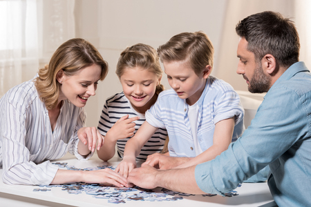 family playing with puzzle on table at home together