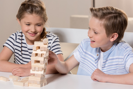 siblings playing Jenga game at home together