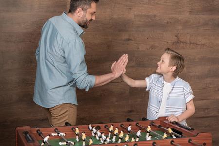 boy playing foosball together with father 版權商用圖片