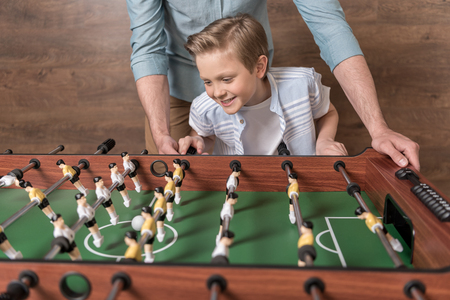 boy playing foosball together with father Stok Fotoğraf