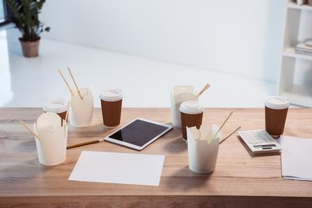 젓가락으로 된 식품 상자, 일회용 커피 컵 및 사무실 테이블에 디지털 타블렛 스톡 콘텐츠
