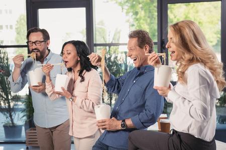 midden oude zakenlieden en onderneemsters die Aziatisch voedsel in bureau eten