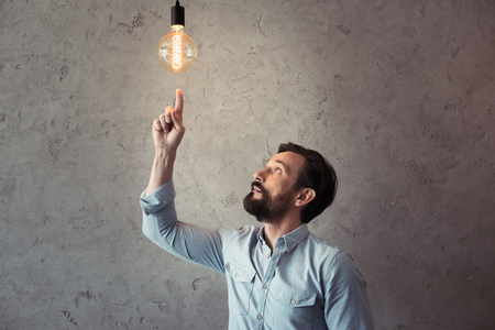 aged man pointing with finger at illuminated light bulb
