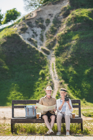 senior couple of travelers sitting together on bench and holding map and instant camera