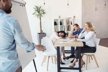 businessman writing on whiteboard while his tired colleagues sitting at table