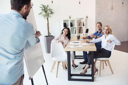 businessman writing on whiteboard while his colleagues sitting at table
