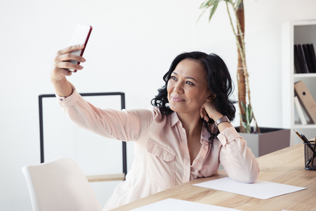 asian businesswoman taking selfie on smartphone while sitting at office