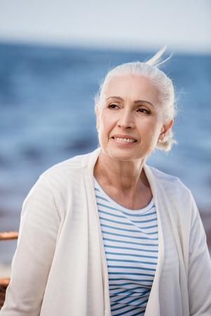 senior dame glimlachend en wegkijken buitenshuis