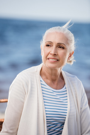 senior lady smiling and looking away outdoors Stock fotó