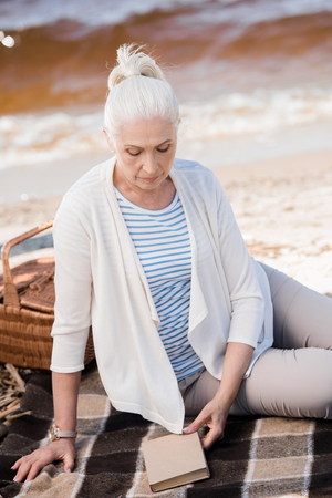 senior woman sitting on plaid with book and picnic basket Stock Photo