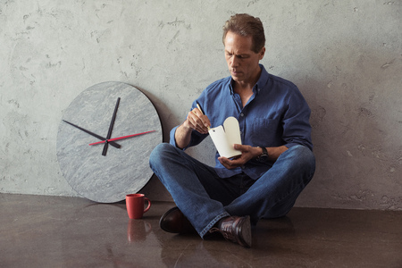 aged man eating noodles while sitting on the floor