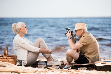 senior man in hat photographing smiling woman with instant camera at beach