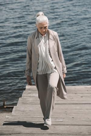 hogere vrouw die op houten gang dichtbij rivier loopt