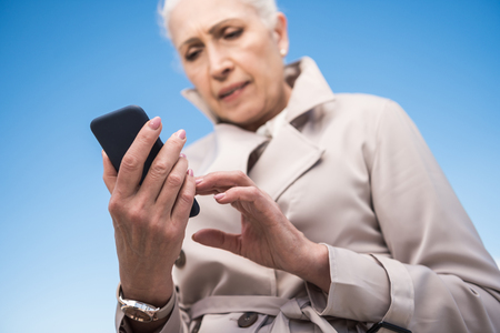 sms: grey haired woman using smartphone outdoors Stock Photo