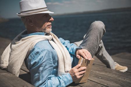Senior man liggend met boek en kijkend op de kade