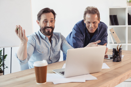 smiling businessmen using laptop and drinking coffee from paper cup in office