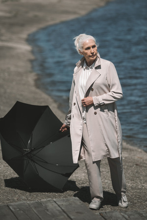 senior woman with black umbrella standing at riverside and looking away