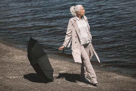 senior vrouw met zwarte paraplu staande op riverside en wegkijken