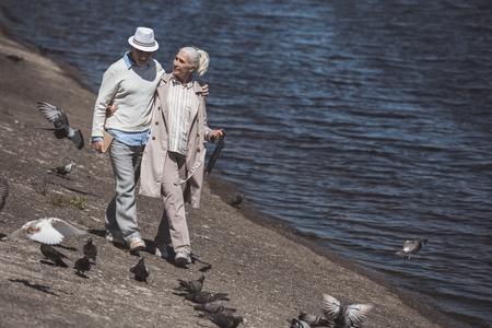 senior paar lopen op de kust rond de rivier overdag