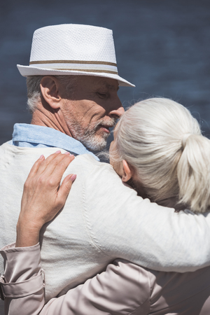 casual elderly couple embracing and able to kiss at daytime