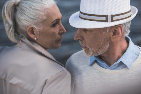 casual grey haired couple able to kiss while standing together