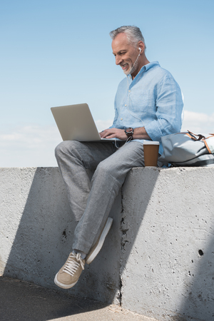 grey haired man working on laptop and listening music in earpods outdoors Stock Photo