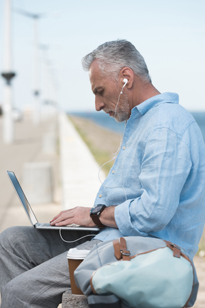 elderly man typing on laptop and listening music in earpods outdoors