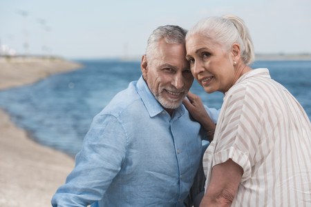 grey haired couple smiling and embracing at quay