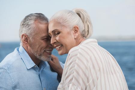 灰色の毛のカップルの笑顔や岸壁で抱きしめて