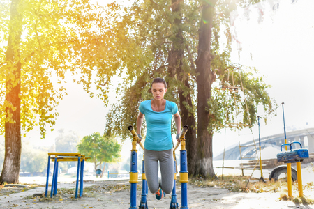 concentrated attractive sportswoman doing push ups outdoors
