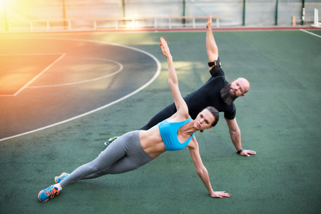 couple doing side plank with raised hands on the stadium
