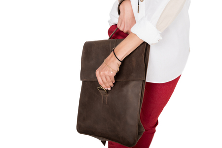 Cropped shot of young woman holding brown leather bag 版權商用圖片