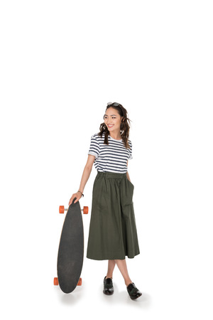 hipster girl in skirt standing with skateboard and looking away