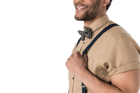 Cropped shot of smiling young man in suspenders and bow tie posing