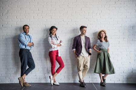 multi-etnische vrienden poseren in stijlvolle kleding in de buurt van bakstenen muur