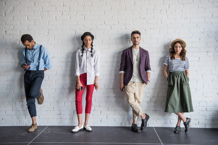 multiethnic friends posing in stylish clothes near brick wall