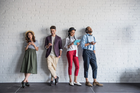 stylish friends using digital devices while standing near brick wall Stock Photo