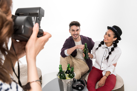 woman with instant camera photographing happy young couple drinking beer together