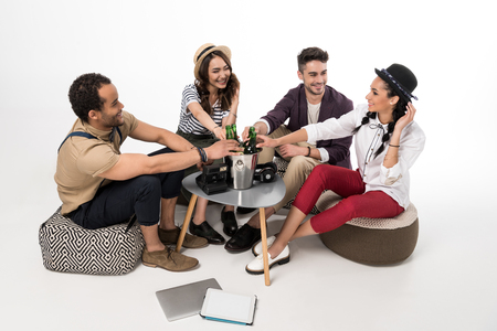young friends sitting together at table with beer bottles in bucket and electronics