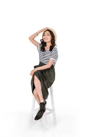 young stylish asian woman posing while sitting on chair