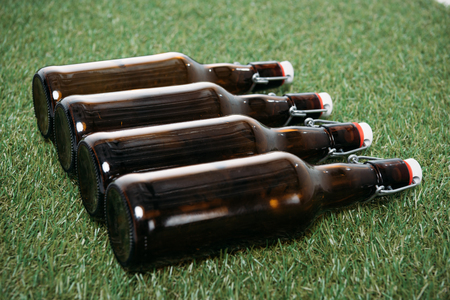 Side view of closed beer bottles lying in row on green grass