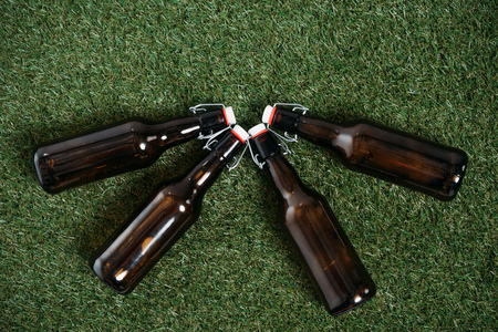 Top view of four closed beer bottles lying together on green grass