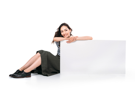 アジアの女性が座っていると空白のボードを押しながらカメラ目線