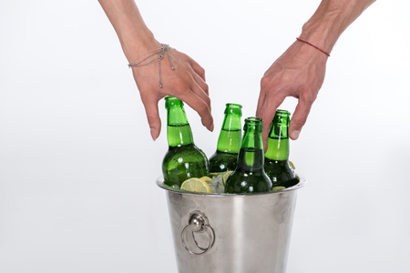Close-up view of human hands and bucket full of ice and beer bottles