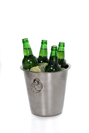 아이스 큐브, 레몬 슬라이스 및 화이트 절연 양동이에 녹색 맥주 병의 근접 촬영보기