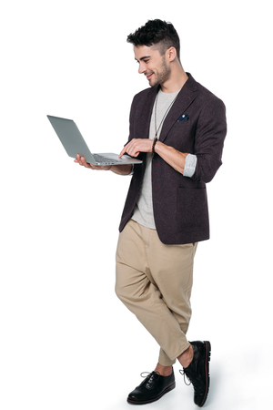 man in casual clothes typing laptop isolated on white