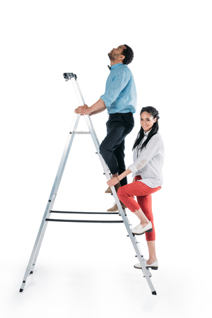 young african american couple climbing on stepladder
