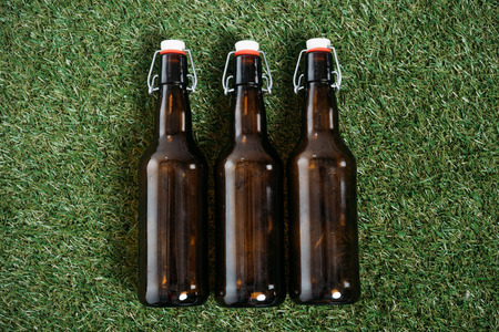 Top view of three glass bottles of beer lying on grass Stock Photo