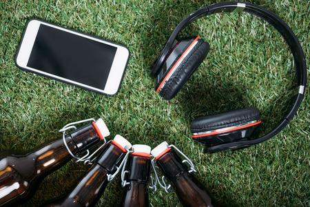 beer bottles with smartphone and headphones lying on green grass Banco de Imagens