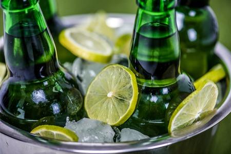 얼음 조각, 맥주 병 및 레몬 슬라이스 양동이의 근접 촬영보기